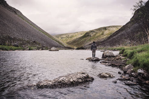 Fly fisherman standing at river bank with mountains, Lakselv, Norway - DHEF00073