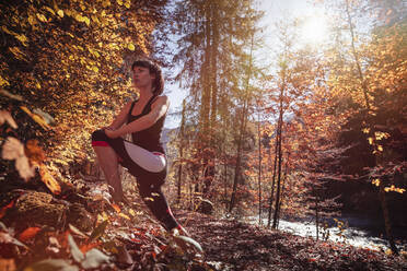 Woman jogging in autumn forest, stretching for warm up - DHEF00089