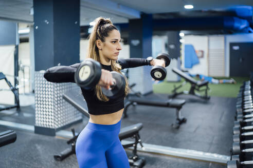 Woman exercising with dumbbells in gym - OCMF00992