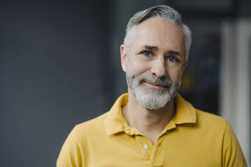 Portrait of smiling mature man with grey beard and blue eyes - KNSF07351