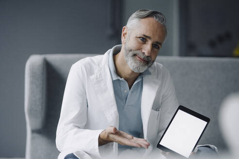 Portrait of smiling doctor with digital tablet at consultation - KNSF07357
