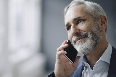 Portrait of smiling mature businessman on the phone - KNSF07369