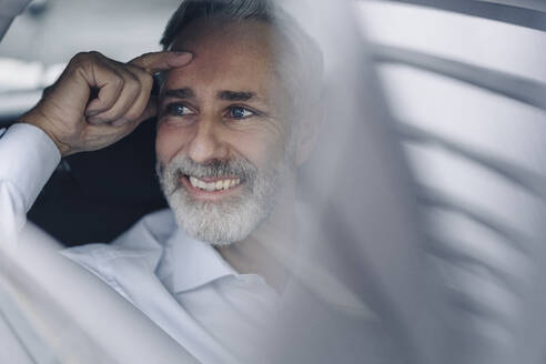 Portrait of smiling mature businessman in his car looking at distance - KNSF07375