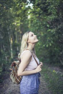 Smiling young woman with backpack in forest watching something - BFRF02183
