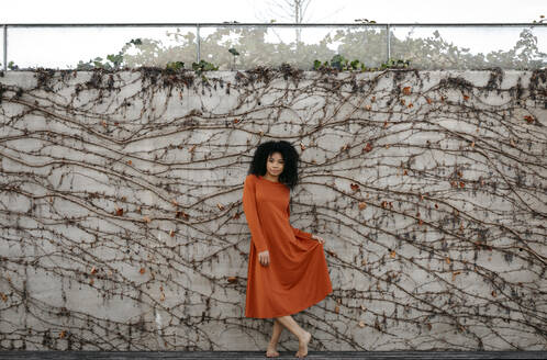 Portrait of a beautiful young woman wearing a dress in front of concrete wall with climbing plant - TCEF00106