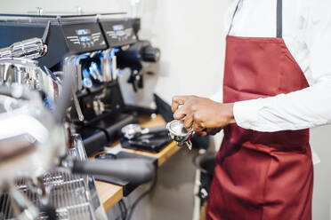 Close-up of barista at work in a coffee shop - OCMF01012