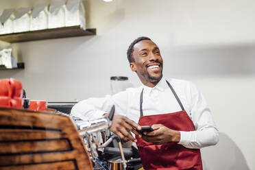 Happy barista holding cell phone in a coffee shop - OCMF01018