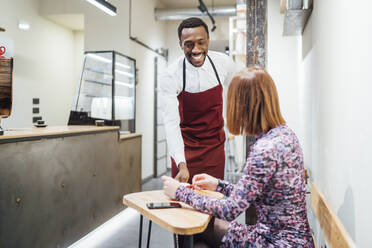Waiter in a cafe serving coffee to woman at table - OCMF01021