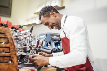Smiling barista preparing a coffee in a coffee shop - OCMF01024