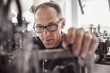 Portrait of focused man working at a machine in a textile factory - SDAHF00058