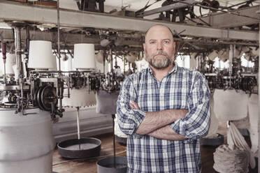 Portrait of a confident mature man in a textile factory - SDAHF00064
