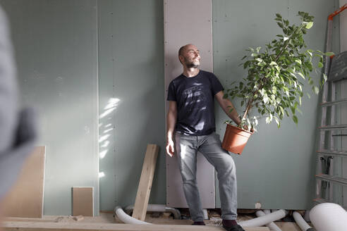 Man holding house plant on construction site at home - KMKF01224