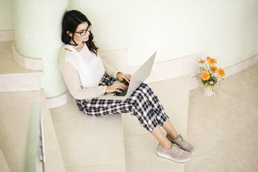 Young woman sitting on stairs using laptop - JRFF04071