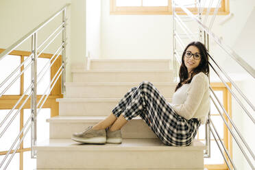 Portrait of smiling young woman sitting on stairs - JRFF04077