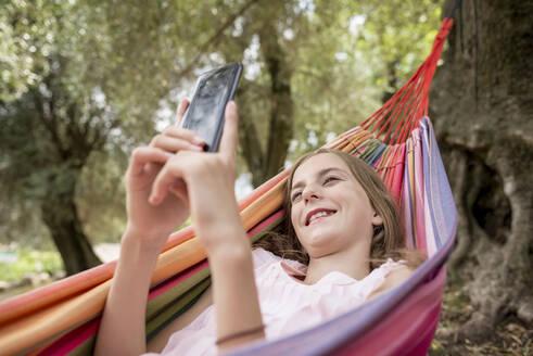 Girl lying in hammock in an olive grove, using smartphone - BFRF02192