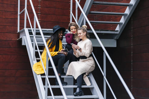 Girlfriends sitting on stairs outdoors looking at mobile phone - DGOF00172