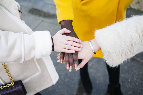 Close-up of three women stacking their hands - DGOF00199