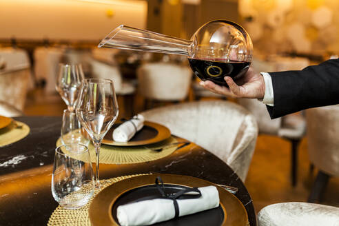 Waiter pouring wine from decanter into glass in fancy restaurant - VABF02574