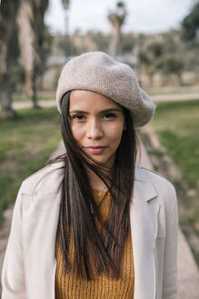 Portrait of young woman with beret in a park - GRCF00142