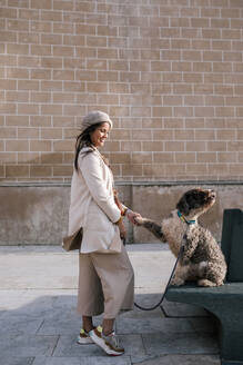 Young woman with her dog in the city giving paw - GRCF00151