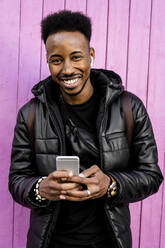 Portrait of smiling man with smartphone and wireless earphones outdoors - RCPF00211