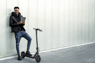 Portrait of happy man with headphones, tablet and e-scooter outdoors - RCPF00220