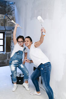 Mother and daughter posing while painting a wall of her new house - DGOF00215