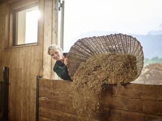 Female farmer pouring straw into barn on a farm - CVF01562