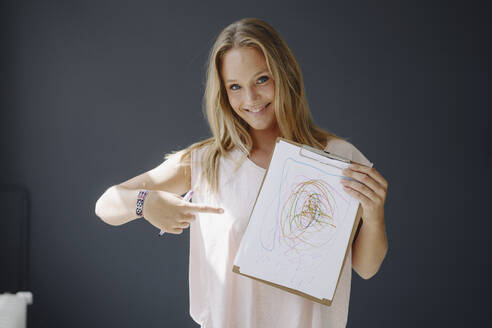 Portrait of blond young woman holding paper with scribbling - KNSF07379