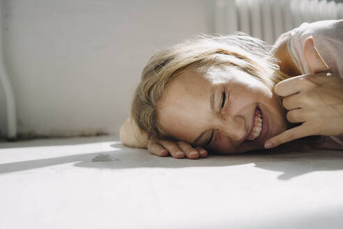 Portrait of happy blond young woman lying on the floor - KNSF07391
