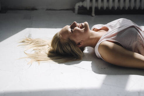 Smiling blond young woman lying on the floor in sunlight - KNSF07394