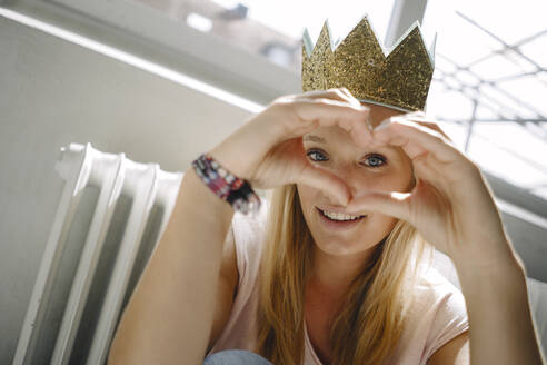 Portrait of blond young woman wearing a crown shaping a heart with her hands - KNSF07403