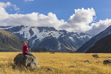 New Zealand, Oceania, South Island, Canterbury, Ben Ohau, Southern Alps (New Zealand Alps), Mount Cook National Park, Aoraki / Mount Cook, Woman sitting on boulder in mountain landscape - FOF11657