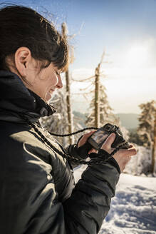 Smling woman checking display of camera in winter at Hornisgrinde, Black Forest, Germany - MSUF00160
