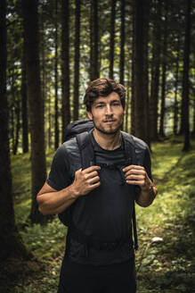 Portrait of a man with backpack on a hiking trip in forest, Karwendel, Tyrol, Austria - MSUF00187