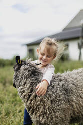 Girl stroking sheep - JOHF06240