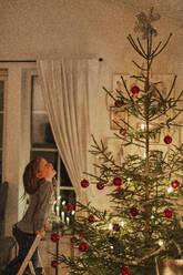 Girl looking at Christmas tree - JOHF06243