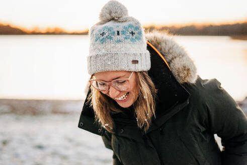 Portrait of woman laughing with snow in her hair at sunset - CAVF73739