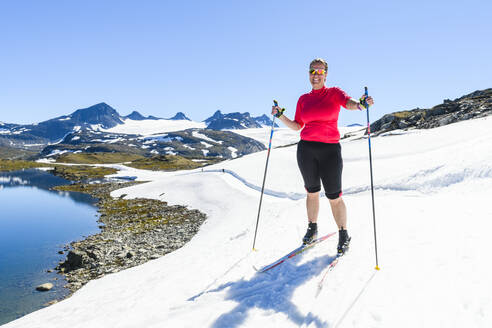Woman cross-country skiing in mountains - JOHF06716