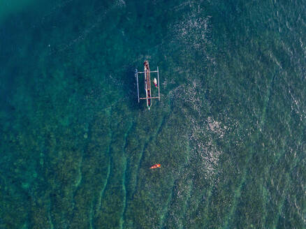 Aerial view of surfer and boat in the ocean - CAVF74105