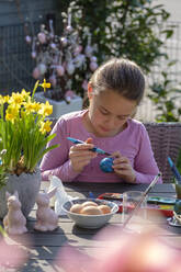 Concentrated girl sitting at garden table painting Easter eggs - LBF02860