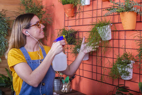 Woman spraying water on Rhipsalis plant on her terrace - RTBF01417