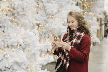 Portrait of smiling young woman standing on the street with Christmas card in front of white Christmas trees - AHSF01841