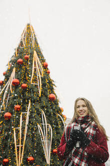 Portrait of smiling young woman with travel mug near Christmas tree on a snowy day - AHSF01844