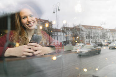 Portrait of happy young woman with mobile phone in a coffee shop looking out of window - AHSF01847