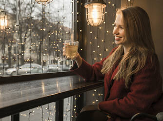 Smiling young woman with cup of tea in a coffee shop - AHSF01850