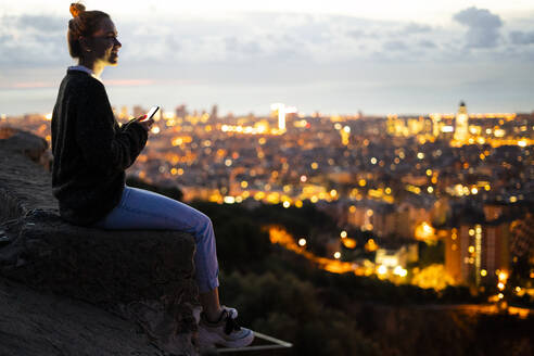 Young woman sitting on railing above the city using cell phone, Barcelona, Spain - GIOF07941