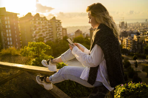 Young woman sitting on railing above the city using cell phone, Barcelona, Spain - GIOF07950