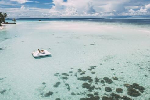 Couple lying on a platform in the sea, Maguhdhuvaa Island, Gaafu Dhaalu Atoll, Maldives - DAWF01217