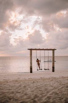 Woman on a swing at the sea at sunset, Maguhdhuvaa Island, Gaafu Dhaalu Atoll, Maldives - DAWF01226